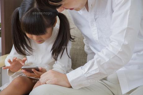 スマホを操作する親子の写真素材 [FYI00922413]