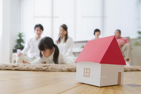団欒する家族と家のミニチュアの写真素材 [FYI00922440]