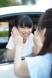 車の窓からバイバイする母娘の写真素材 [FYI00922879]