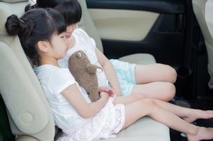 車の中で眠る姉妹の素材 [FYI00922885]
