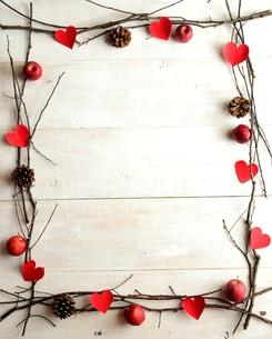 赤いハートの切り絵と林檎とまつぼっくりのフレーム  白木材背景の写真素材 [FYI00922926]
