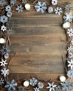雪の結晶の切り絵とキャンドルのフレーム 黒木材背景の写真素材 [FYI00922935]