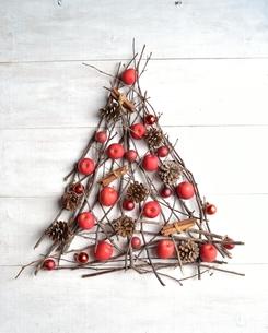 林檎とシナモンスティックとまつぼっくりのクリスマスツリー 白木材背景の写真素材 [FYI00923234]