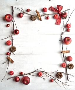 林檎とシナモンスティックと赤いクリスマスオーナメント 白木材背景の写真素材 [FYI00923237]