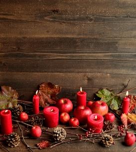 林檎と落葉と赤いキャンドル 黒木材背景の写真素材 [FYI00923261]