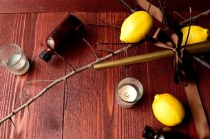 レモンとキャンドルとエッセンシャルオイルボトル 茶色木材背景の写真素材 [FYI00924120]
