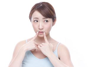 口元を気にする若い女性の写真素材 [FYI00924245]