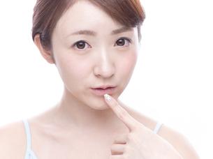 口元を気にする若い女性の写真素材 [FYI00924247]