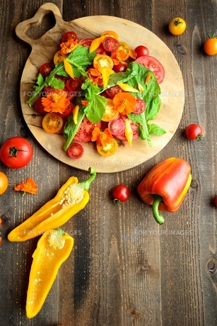 まな板に盛り合わせたパプリカとトマトとルッコラのサラダの写真素材 [FYI00924410]