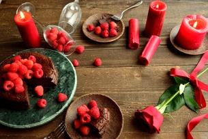ラズベリーのチョコレートケーキと赤い薔薇とキャンドルの写真素材 [FYI00924429]
