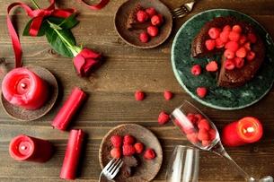 ラズベリーのチョコレートケーキと赤い薔薇とキャンドルの写真素材 [FYI00924435]