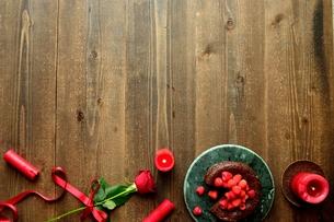 ラズベリーのチョコレートケーキと赤い薔薇とキャンドルの写真素材 [FYI00924439]
