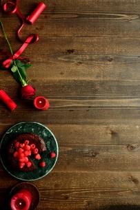ラズベリーのチョコレートケーキと赤い薔薇とキャンドルの写真素材 [FYI00924440]