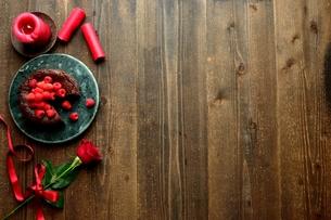 ラズベリーのチョコレートケーキと赤い薔薇とキャンドルの写真素材 [FYI00924441]