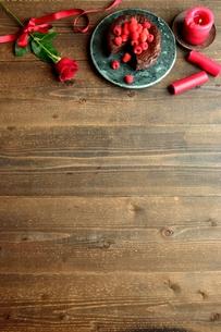 ラズベリーのチョコレートケーキと赤い薔薇とキャンドルの写真素材 [FYI00924442]
