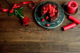 ラズベリーのチョコレートケーキと赤い薔薇とキャンドルの写真素材 [FYI00924443]