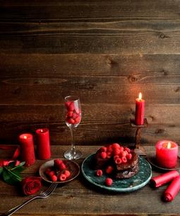 ラズベリーのチョコレートケーキと赤い薔薇とキャンドルの写真素材 [FYI00924444]