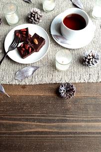 チョコレートブラウニーとコーヒーとキャンドル ニット生地背景の写真素材 [FYI00924506]