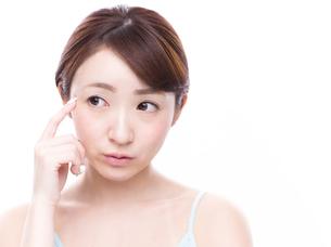 こめかみを指差す若い女性の写真素材 [FYI00924583]