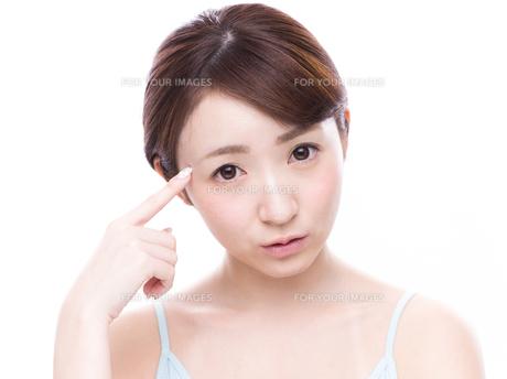 こめかみを指差す若い女性の写真素材 [FYI00924585]