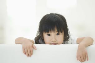 ソファの背もたれから顔を出す女の子の素材 [FYI00934586]