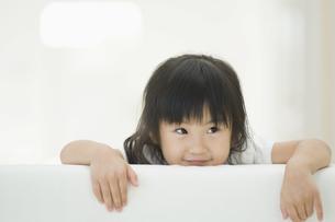 ソファの背もたれから顔を出す女の子の素材 [FYI00934593]