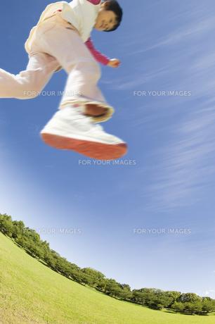 新緑の公園でジャンプする女の子の素材 [FYI00934646]