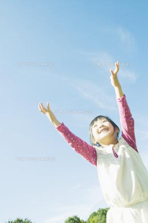 青空に向かって両手をあげる女の子の素材 [FYI00934703]