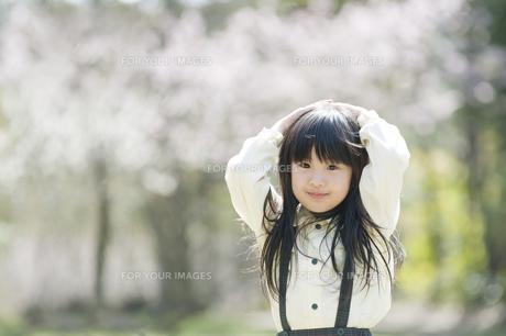両手を頭に乗せて微笑む女の子の素材 [FYI00934727]
