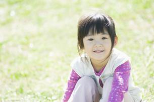 芝生に座って微笑む女の子の素材 [FYI00934780]