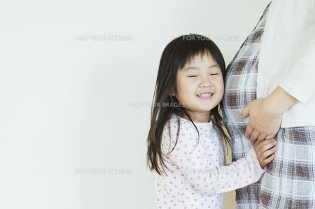 妊婦のお腹に耳を当てる女の子の素材 [FYI00934788]