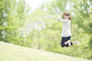 新緑の中をジャンプする女性の素材 [FYI00934891]