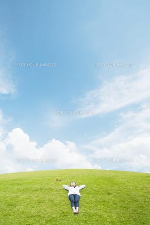 草原で寝転ぶ女性の素材 [FYI00934965]