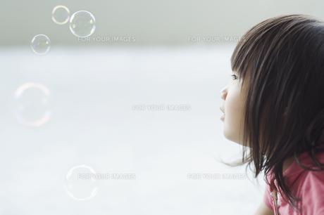 シャボン玉を見つめる女の子の素材 [FYI00934978]