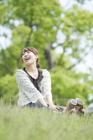 草原に座って笑う女性の素材 [FYI00935008]