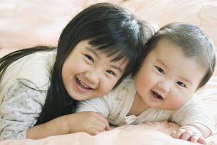 寝転ぶ笑顔の姉弟の素材 [FYI00935086]