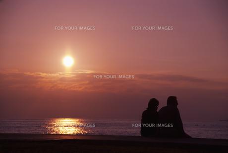 夕陽とカップルのシルエットの素材 [FYI00935207]