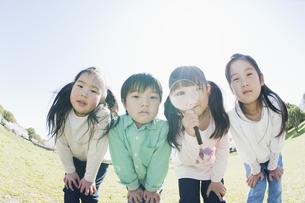 虫眼鏡をのぞく子供達の素材 [FYI00935220]