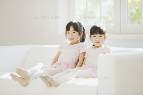 ソファでくつろぐバレエ姿の二人の女の子の素材 [FYI00935445]