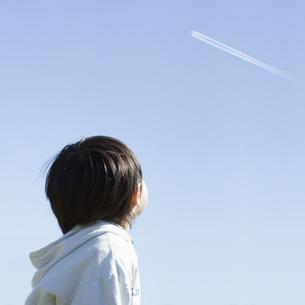 飛行機雲を見上げる男の子の後姿の素材 [FYI00935492]