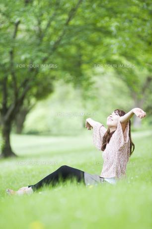 新緑の中で伸びをする女性の素材 [FYI00935578]
