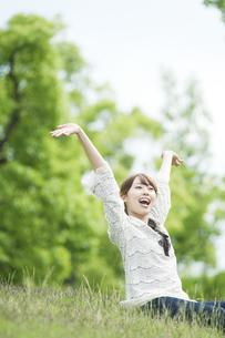 草原に座って伸びをする女性の素材 [FYI00935589]