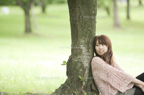 樹にもたれて微笑む女性の素材 [FYI00935599]