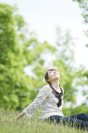 草原に座って笑う女性の素材 [FYI00935608]
