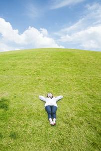 草原で寝転ぶ女性の素材 [FYI00935635]
