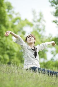 草原に座って伸びをする女性の素材 [FYI00935657]