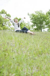 草原に座って伸びをする女性の素材 [FYI00935690]