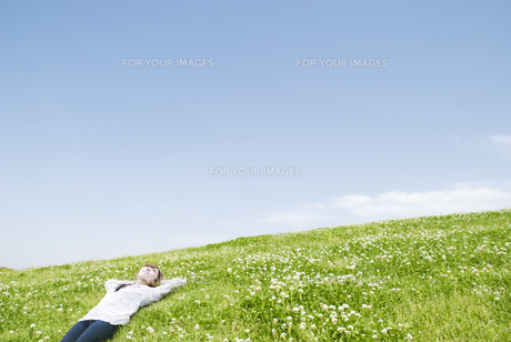 草原で寝転ぶ女性の素材 [FYI00935693]