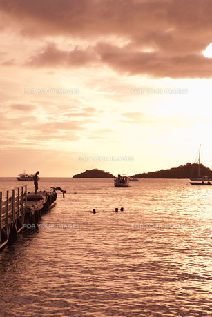 桟橋から飛び込みをする人々 夕景の素材 [FYI00940525]