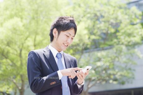 スマートフォンを操作するビジネスマンの素材 [FYI00941503]